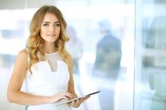 看照相机的白肤金发的女实业家 免版税图库摄影