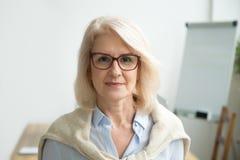 看照相机的确信的年迈的女实业家佩带的玻璃, 免版税库存图片