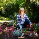 看照相机的美丽的女性花匠微笑和拿着木板箱准备好有很多的花在她的庭院里被种植 免版税图库摄影
