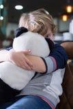 看照相机的逗人喜爱的小男孩,当拥抱熊猫玩具时 免版税库存照片