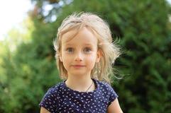 看照相机的逗人喜爱的矮小的白肤金发的女孩特写镜头画象惊奇在夏日期间在公园 愉快的孩子 库存照片