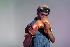 看照相机的金黄拳击手套的时髦的年轻非裔美国人的人 库存照片