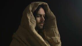 看照相机的长袍的耶稣基督隔绝在黑暗的背景,上帝的儿子 股票视频
