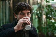 看照相机的饮用的咖啡的年轻英俊的人 库存图片
