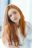 看照相机的浴巾的红头发人妇女 免版税图库摄影