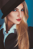 看照相机的黑帽会议的迷人的白肤金发的妇女 免版税图库摄影