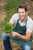 看照相机的年轻愉快的农夫,当拿着菜时 库存图片