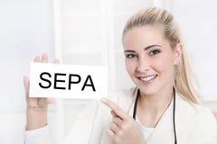 看照相机的年轻白肤金发的妇女拿着SEPA标志 库存图片