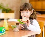 看照相机的画象女小学生,当吃午餐在期间时 库存照片