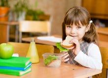 看照相机的画象女小学生,当吃午餐在期间时 库存图片
