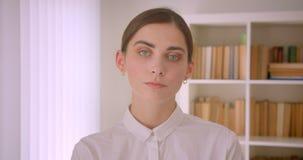 看照相机身分的年轻成功的白种人女实业家特写镜头画象在有书架的办公室  股票录像