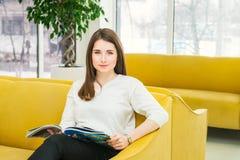 看照相机,坐明亮的黄色沙发在现代等待的大厅里和读杂志的女孩画象 好客 免版税库存照片