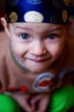 看照相机,蓝眼睛的小男孩明亮在班丹纳花绸 免版税库存照片