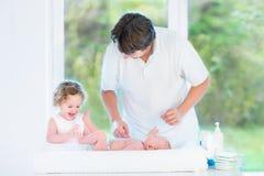 看父亲和小孩姐妹的逗人喜爱的新出生的婴孩 免版税图库摄影
