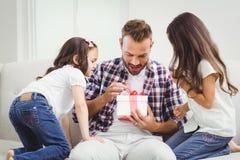 看父亲开头礼物的好奇女孩 免版税库存照片