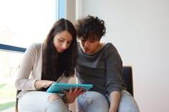 看片剂个人计算机的两个女学生 免版税库存图片