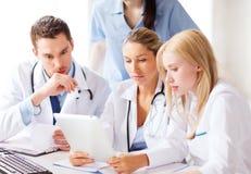 看片剂个人计算机的小组医生 免版税图库摄影