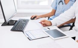 看片剂个人计算机的小组医生 免版税库存照片