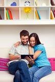 看片剂个人计算机的年轻夫妇 免版税库存图片