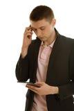 看片剂和电话的商人 库存图片