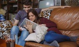 看片剂的年轻夫妇坐沙发 免版税库存图片