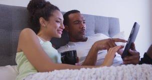 看片剂计算机和喝咖啡Slo mo的清早夫妇在床上 免版税库存图片