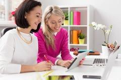 看片剂计算机的两名妇女,当工作在办公室时 免版税库存图片