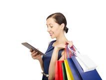 看片剂计算机的购物妇女 免版税图库摄影