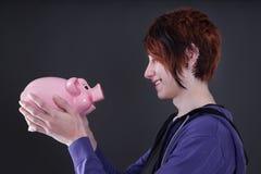 看猪钱箱的男孩 免版税库存照片