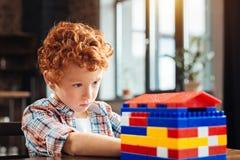 看玩具房子的被集中的蓝眼睛的男孩 免版税库存照片