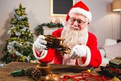 看玩具汽车的微笑的圣诞老人在客厅 免版税库存照片