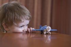 看玩具飞机的男孩 免版税库存图片