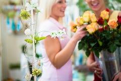 看玫瑰的花束在花店的两名妇女 图库摄影