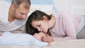 看甜睡觉的婴孩的愉快的父母在卧室 股票视频