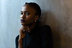 看用手在下巴下,灰色背景的体贴的年轻黑人妇女特写镜头  免版税库存图片