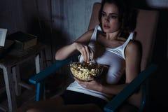 看电视用玉米花的妇女 免版税库存照片