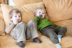 看电视的二个小兄弟男孩室内 免版税库存照片