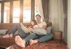 看电视的亚洲夫妇在家坐快乐的长沙发 免版税库存照片