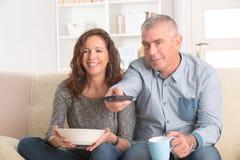 看电视的夫妇在他们的客厅 库存图片