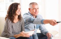 看电视的夫妇在他们的客厅 免版税库存照片