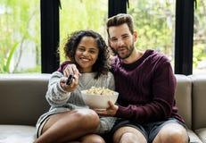 看电视的夫妇食用玉米花 库存图片
