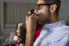看电视的家庭戴3D眼镜和吃玉米花 免版税图库摄影
