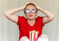 看电视的少妇坐有3d玻璃和流行音乐的长沙发 免版税图库摄影