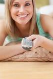 看电视的快活的白肤金发的妇女位于在楼层上 免版税库存照片