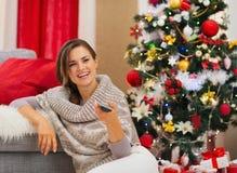 看电视的愉快的妇女在圣诞树附近 免版税库存图片