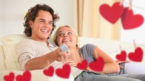 看电视的愉快的年轻夫妇 股票录像