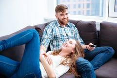 看电视的笑的夫妇 库存图片