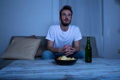 看电视的年轻人在与芯片和啤酒的夜间 库存照片
