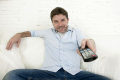 看电视的年轻愉快的人在家坐看起来客厅的沙发放松享用电视 免版税库存图片
