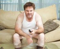 看电视的终日懒散在家的人 图库摄影